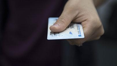 Человек передает биометрический паспорт гражданина Кыргызской Республики