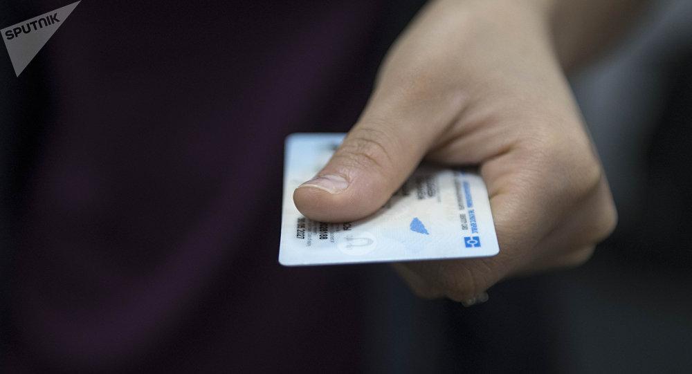 Человек передает биометрический паспорт гражданина Кыргызской Республики. Архивное фото