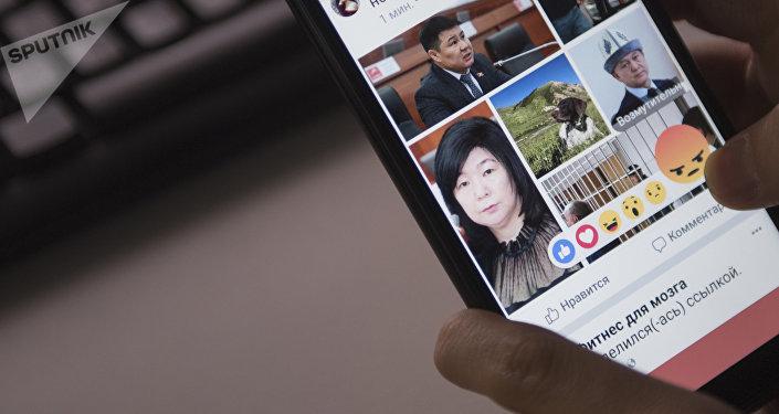 Парень просматривает страницу социальной сети на телефоне. Архивное фото