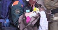 Спасатели достают 11-месячную девочку из-под завалов дома в Магнитогорске.