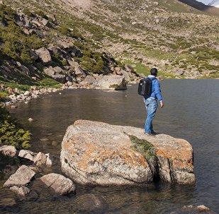 Путешественник у горного озера в Кыргызстане. Архивное фото