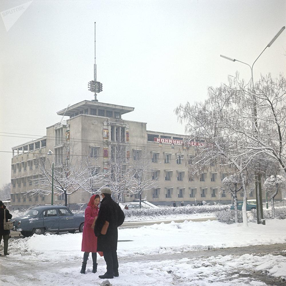 50 жыл мурунку Бишкектин көчөлөрү: кызыл жоолук салынган кыз, папкасын колтугуна кысып бийкеч менен баарлашып турган жигит жана көк түстөгү Волга автоунаалары