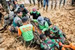 Спасатели несут тело после оползня в районе Чисолок в Сукабуми, провинция Западная Ява. Индонезия, 1 января 2019 года