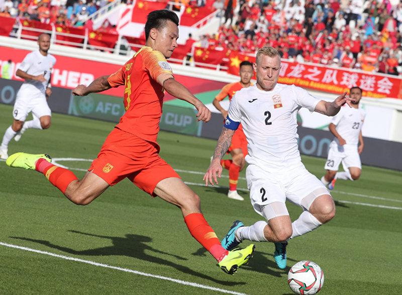 Нападающий Китая Ши Ке (слева) борется за мяч с защитником Киргизии Валерием Кичиным во время футбольного матча АФК 2019 по футболу между сборными Кыргызстана и Китая на стадионе имени Халифы бен Заида в Аль-Айне 7 января 2019 года.