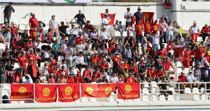 Кытайлык атаандаштары менен оюн өткөрүп жаткан кыргызстандык футболчуларды жүздөн ашуун күйөрман сүрөөнгө алып турду