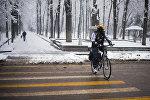Велосипедист едет по проспекту Эркиндик во время снегопада в Бишкеке. Архивное фото