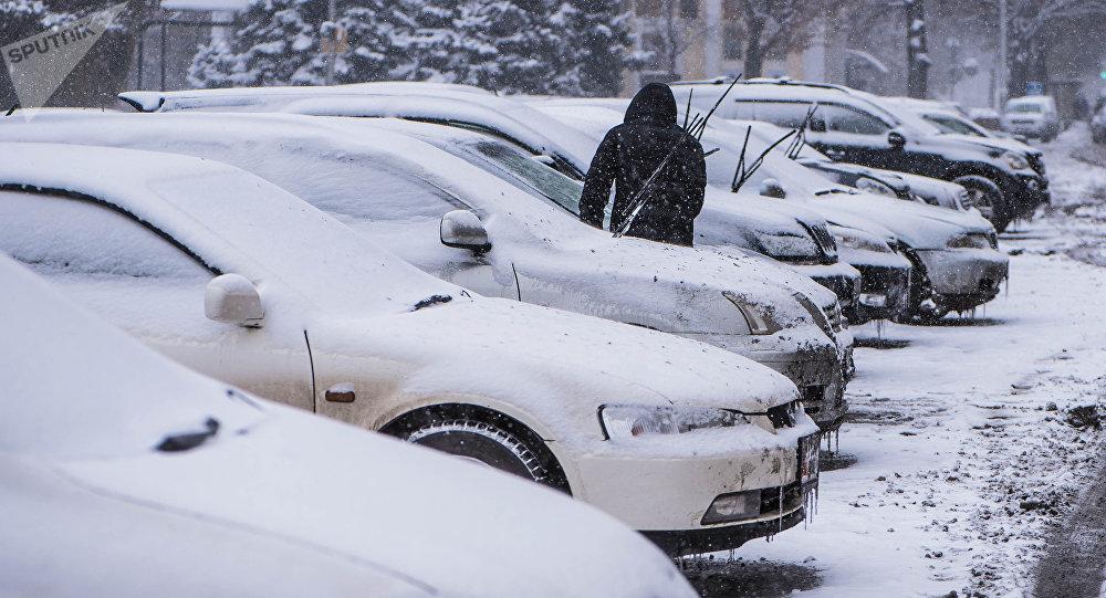 Автомобилист у своего транспорта во время снегопада в Бишкеке. Архивное фото