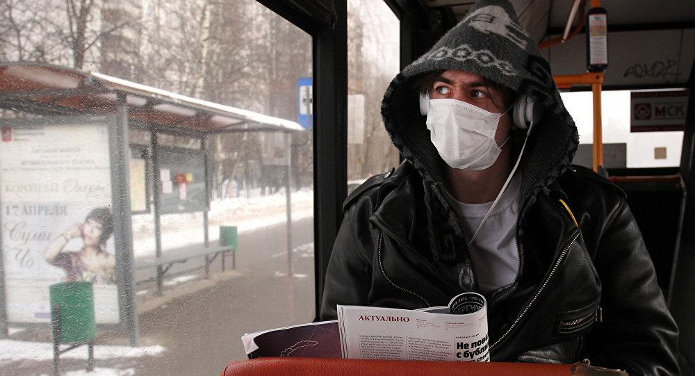 Молодой человек в защитной маске в автобусе. Архивное фото