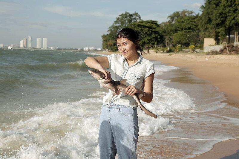 Журналист Sputnik Кыргызстан Бегимай Бакашева держит маленькую акулу в Таиланде