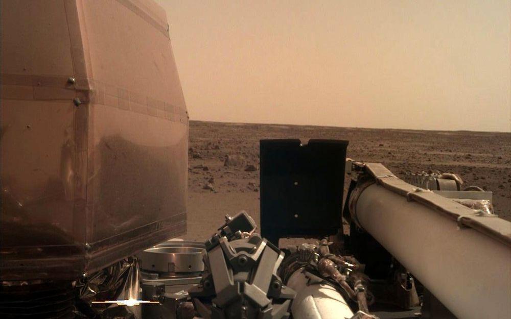 Первая фотография, полученная камерой руки зонда InSight после ее включения