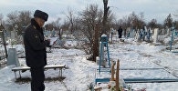 Сотрудник милиции на месте погрома на православном кладбище в Ананьево