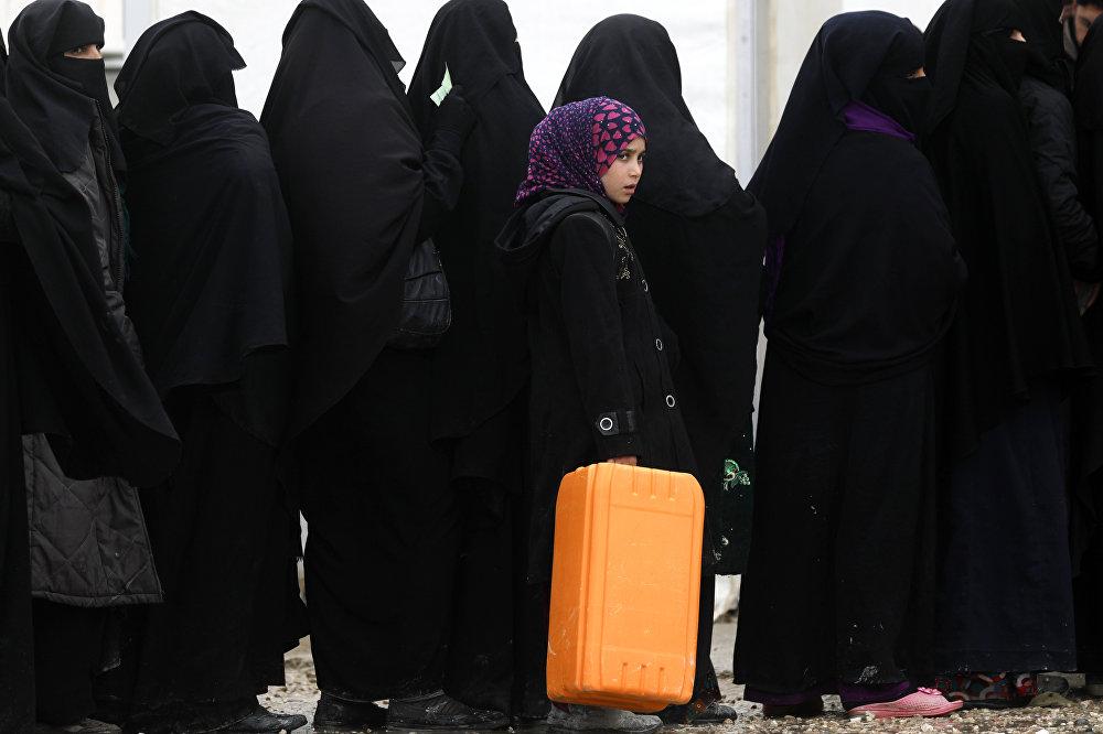 Качкындар лагеринде гуманитардык жардам алуу үчүн кезекте турган сириялык аялдар