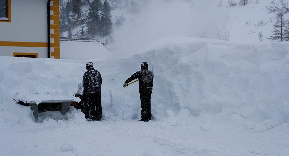 Двое рабочих убирают снег после сильного снегопада в Обертауэрне, Австрия, 10 января 2019 года
