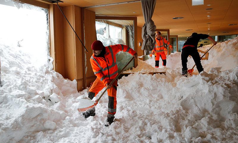 Рабочие убирают снег из ресторана после лавины на горнолыжном курорте Сантис-Швегальп в Швейцарии. 11 января 2019 года