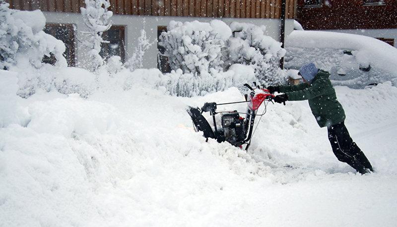 Мужчина убирает снег после сильного снегопада в Варнгау под Мюнхеном, Германия, 6 января 2019 года