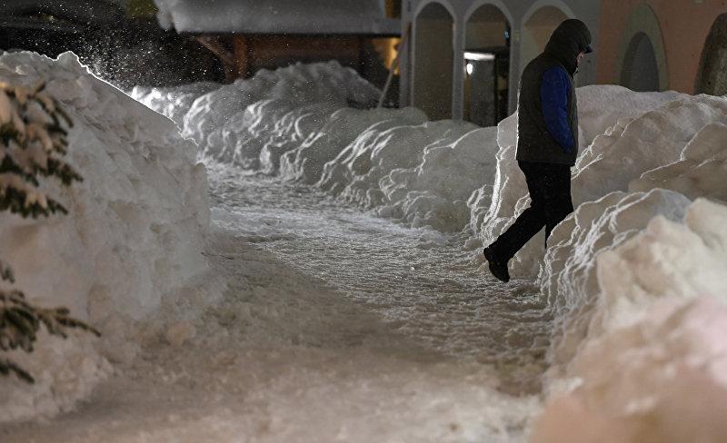 Мужчина идет по груде снега в пешеходной зоне в центре Берхтесгадена, Германия, 10 января 2019 года