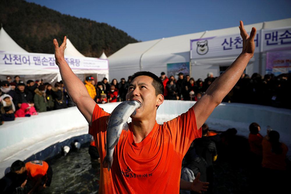 Түштүк Кореяда өткөн Форель фестивалынын катышуучусу кармап алган балыгы менен