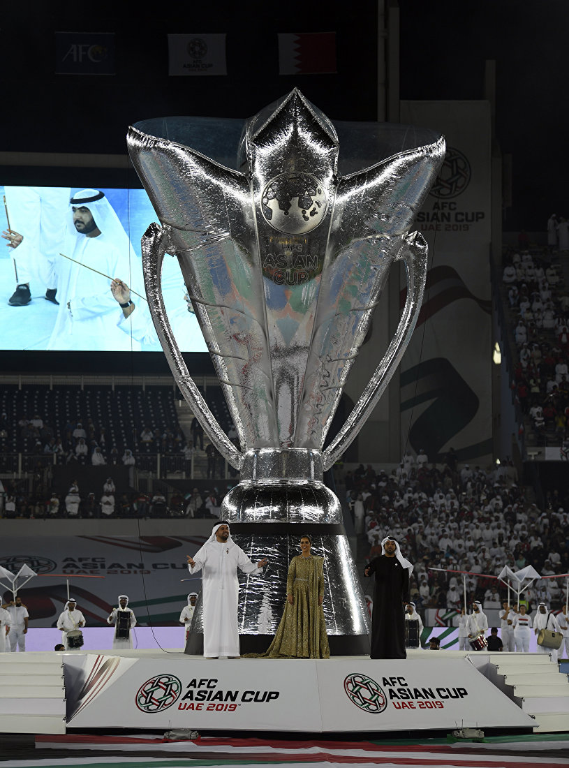 Певцы выступают под гигантской копией Кубка Азии АФК 2019 перед началом футбольного матча между Объединенными Арабскими Эмиратами и Бахрейном на спортивном городском стадионе Зайед в Абу-Даби 5 января 2019 года.