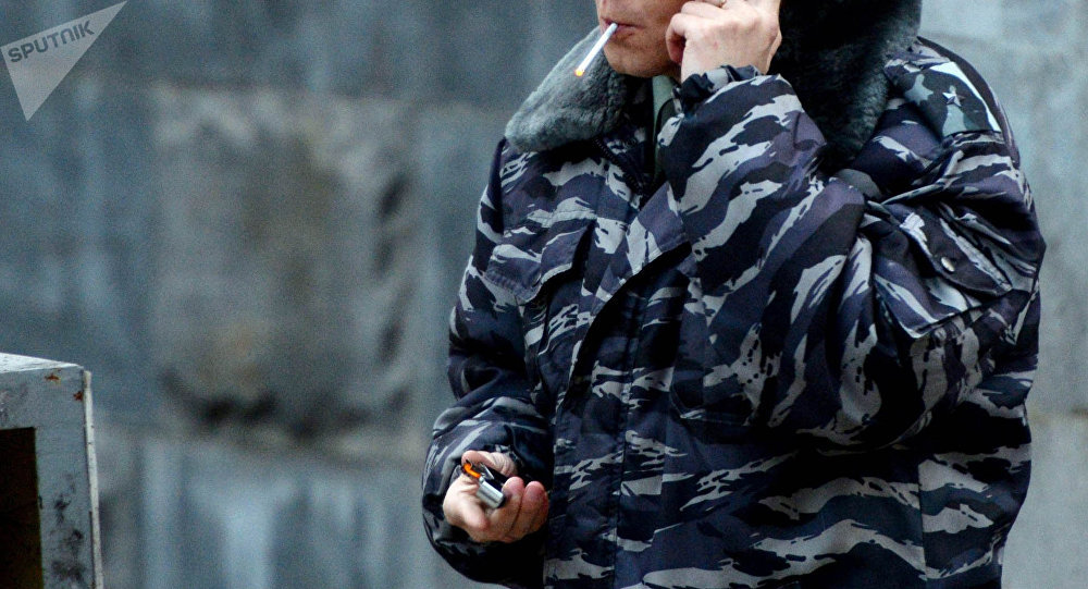 Сотрудник в форме курит сигарету. Архивное фото