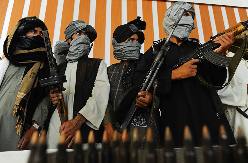 Бывшие боевики Талибана стоят со своим оружием во время церемонии после присоединения к афганским правительственным войскам в Герате 7 августа 2013 года
