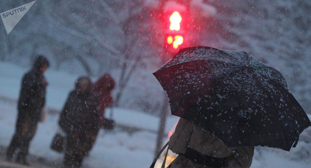 Прохожие по улице во время снегопада. Архивное фото