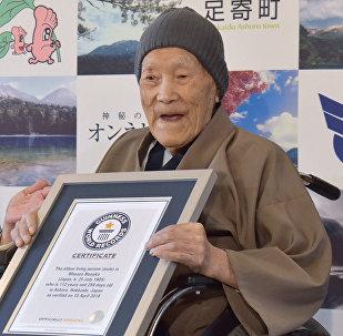 Масасо Нонака из Японии которому 112 лет, получает сертификат на звание старейшего мужчины-рекордсменки Книги рекордов Гиннеса от Эрики Огавы. вице-президента Японского рекорда Гиннеса, в Ашоро, префектура Хоккайдо. 10 апреля 2018 года. Нонака родился 25 июля 1905 года.
