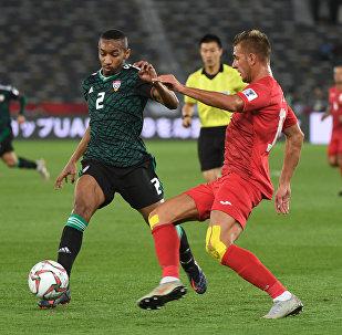 Полузащитник Объединенных Арабских Эмиратов Али Салмин и нападающий сборной Кыргызстана Виталий Люкс во время раунда 16-го тура Кубка Азии по футболу между сборными командами ОАЭ и Кыргызстана, который проходит на стадионе Zayed Sports City в Абу-Даби 21 января 2019 года.