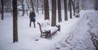 Девушка идет по проспекту Эркиндик во время обильного снегопада в Бишкеке