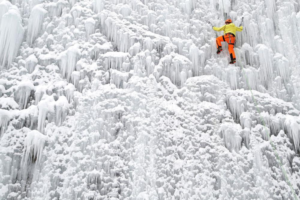 Мужчина поднимается по искусственной ледяной стене, расположенной в городе Либерец, Чешская Республика