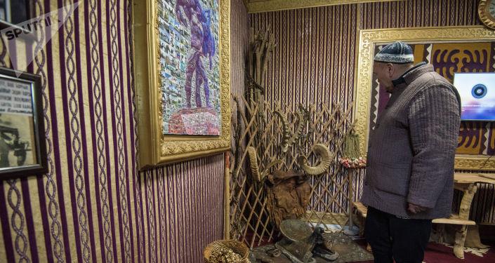 Мужчина рассматривает экспонаты открытии музея кыргызскому силачу Кожомкулу Каба уулу в одноименном дворце спорта в Бишкеке