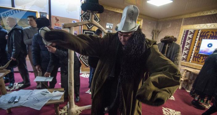 Мужчина примеряет верхнюю одежду кыргызского силача Кожомкула Каба уулу у музее во дворце спорта в Бишкеке
