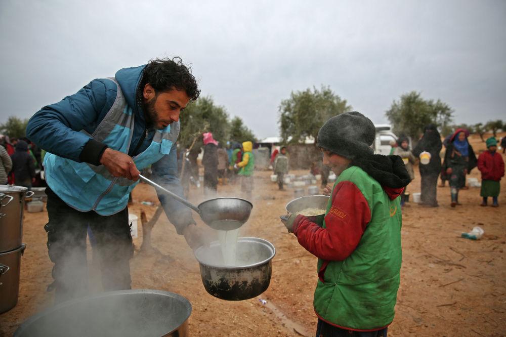 Сириянын Алеппо провинциясындагы лагерде тамак тараткан кызматкер