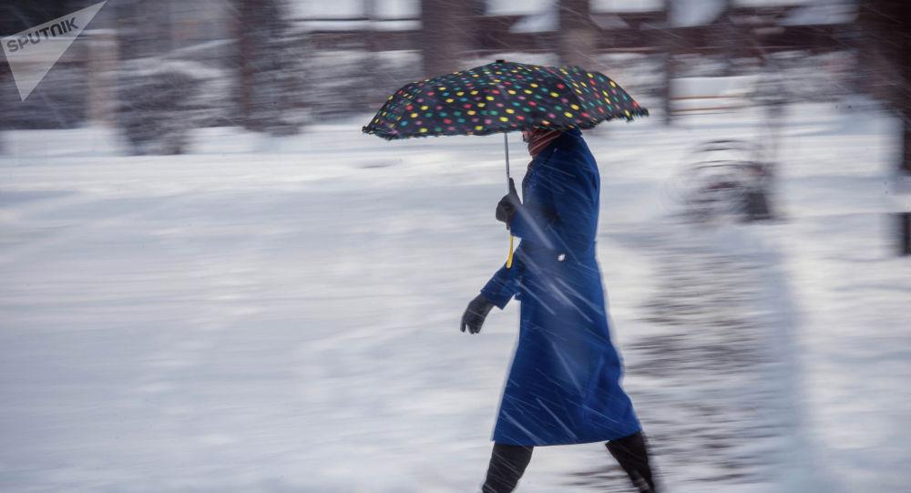 Девушка с зонтом на одному из улиц Бишкека во время снегопада