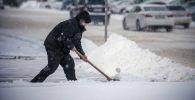 Мужчина убирает снег во время обильных осадков. Архивное фото