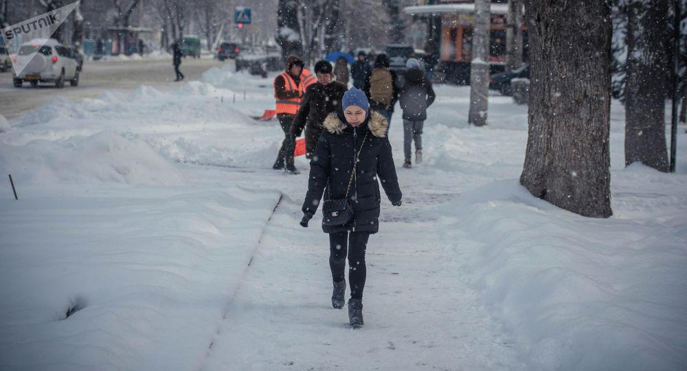 Девушка идет по проспекту Эркиндик во время снегопада в Бишкеке. Архивное фото