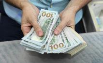 Мужчина считает доллары США. Архивное фото