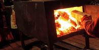 Женщина разводит огонь в печке. Архивное фото