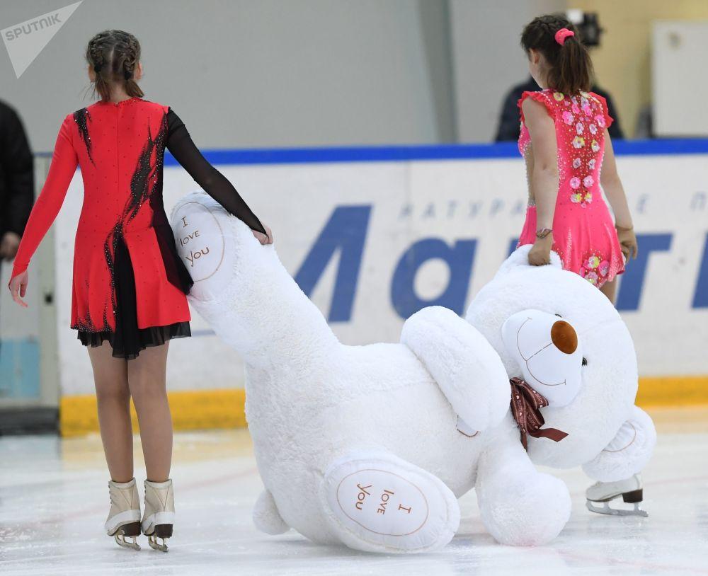 Девушки уносят игрушечного мишку с ледовой площадки после выступления фигуристок