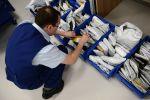 Сотрудник  отделения почты разбирает посылки. Архивное фото