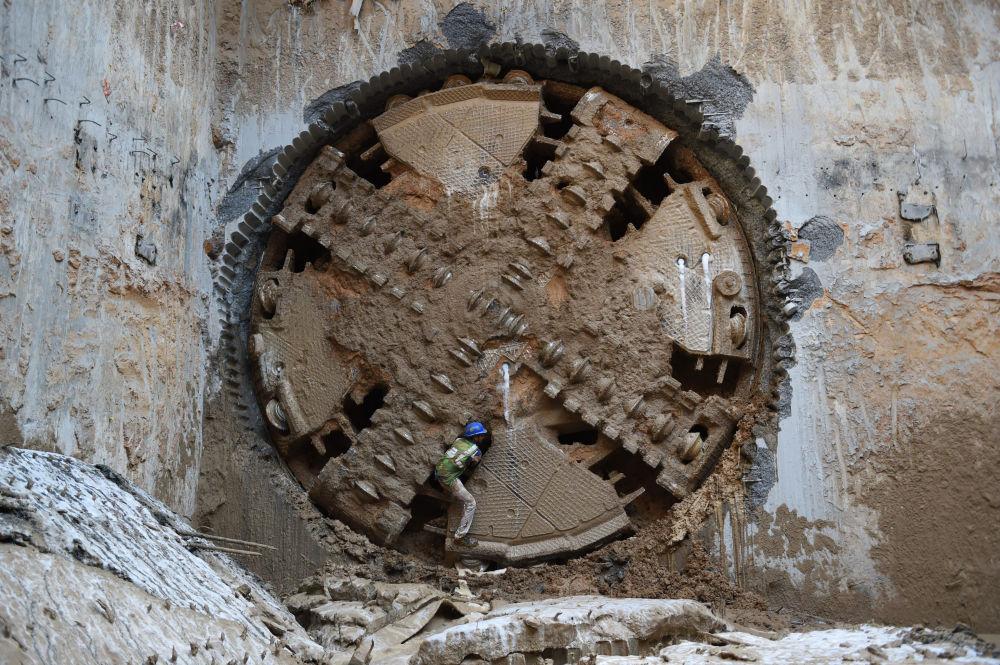 Индиялык жумушчу Ахмадабаддагы Gujarat Metro Rail Corporation Limited туннелинен чыгып жатат