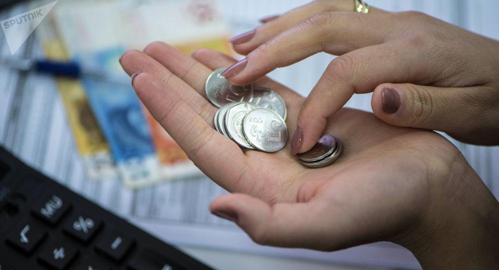 Женщина пересчитывает монеты. Архивное фото