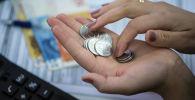 Женщина считает монеты в руках. Архивное фото