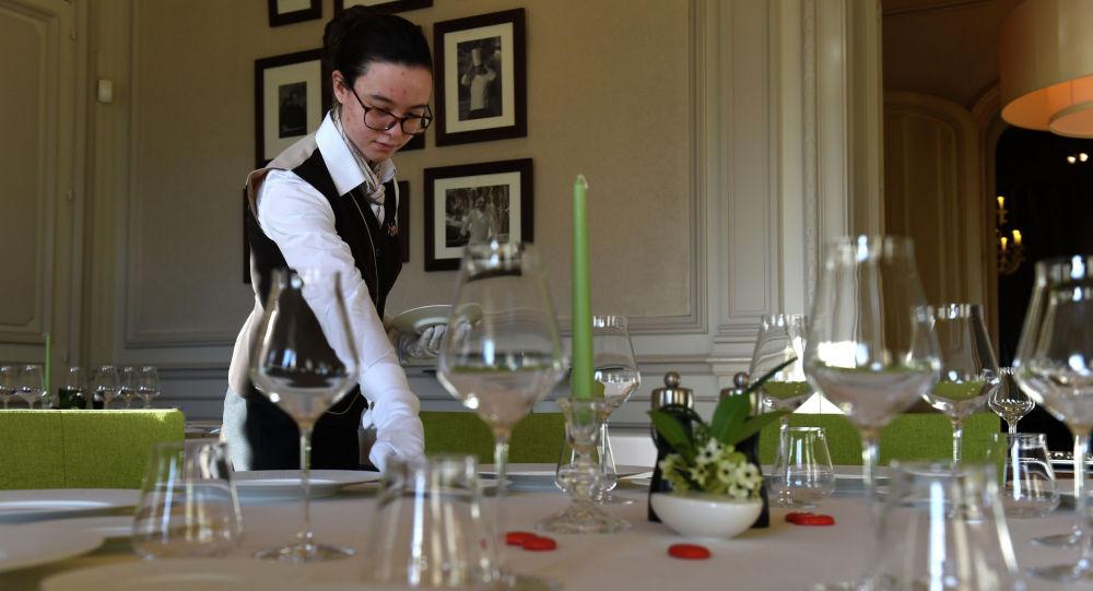 Ресторандагы официант столду меймандарга даярдоо кезинде. Архивдик сүрөт