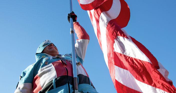 Мужчина, в форме Капитана Америка, гуляет с гигантским американским флагом возле Окружного суда США в Вашингтоне. Архивное фото