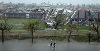 Люди идут по затопленной улице рядом со зданиями, поврежденными тропическим циклоном Идаи на юге Африки, Мозамбик, 17 марта 2019 года