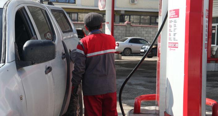 Мужчина заправляет авто в автозаправочной станции в Оше