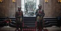 Актеры изображающие рыцарей, охраняют Железный Трон на интерактивной инсталляции Игра престолов. Архивное фото
