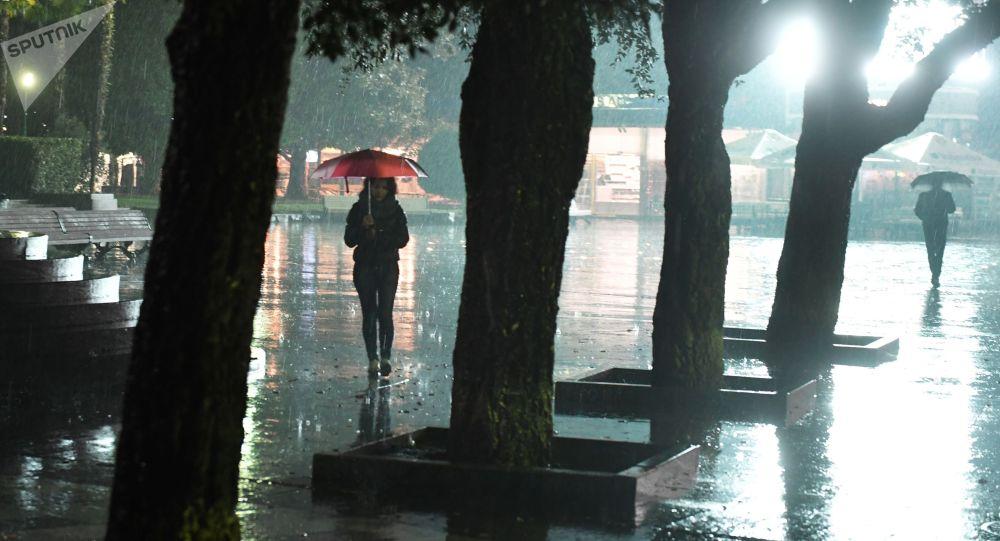 Прохожие на улице во время дождя. Архивное фото