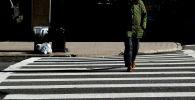 Мужчина переходит дорогу на пешеходном переходе. Архивное фото