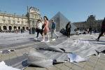 Посетители идут мимо бумажной инсталляции, установленной по случаю 30-летия Лувра в Париже. 31 марта 2019 года